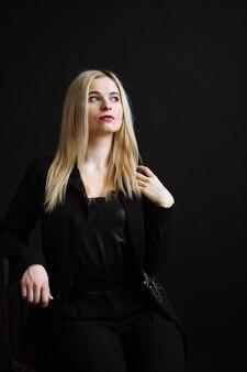 Schöne junge frau in der schwarzen jacke auf schwarzem hintergrund. hübsches blondes mädchen