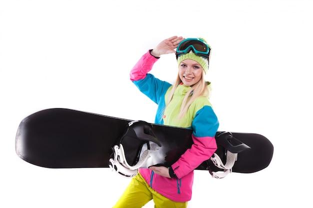 Schöne junge frau in der skiausstattung und in den skibrillen halten snowboard