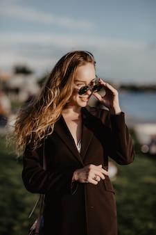 Schöne junge frau in der sonnenbrille in der stadt bei sonnenuntergang