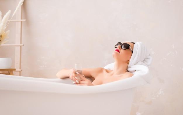 Schöne junge frau in der sonnenbrille mit einem glas champagner im badezimmer.