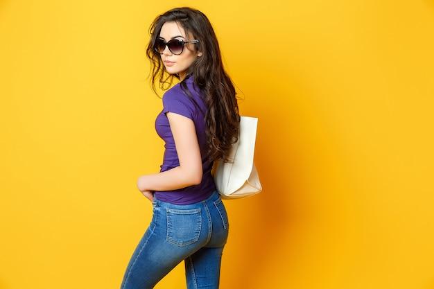 Schöne junge frau in der sonnenbrille, purpurrotes hemd, blue jeans, die mit tasche auf gelbem hintergrund aufwerfen