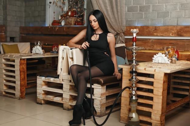 Schöne junge frau in der stilvollen schwarzen kleidung, die auf einem sofa sitzt und eine wasserpfeife raucht