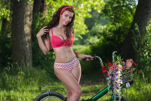 Schöne junge frau in der wäsche draußen mit fahrrad und blumen