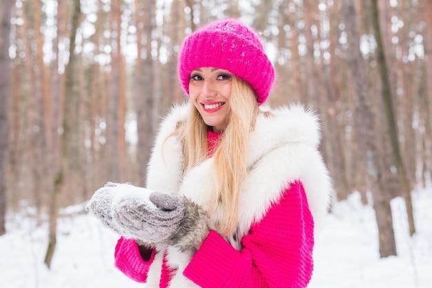 Schöne junge frau in der warmen jacke im winterpark