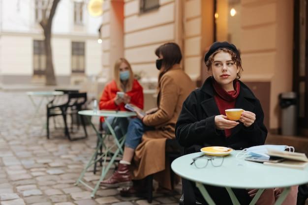 Schöne junge frau in der warmen kleidung, die heißen kaffee an der caféterrasse trinkt.