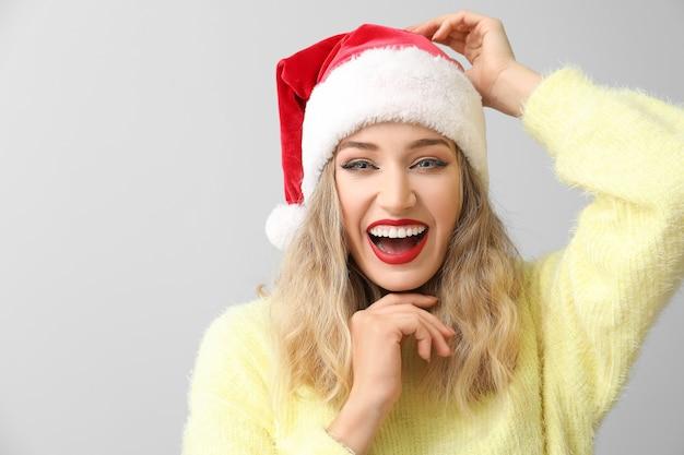 Schöne junge frau in der weihnachtsmütze auf licht