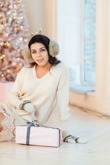 Schöne junge frau in der weißen kleideraufstellung