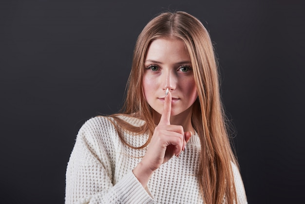 Schöne junge frau in der weißen strickjacke und in den jeans lokalisiert auf schwarzem hintergrund