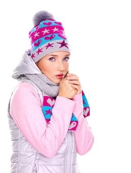 Schöne junge frau in der winterkleidung, die ihre hände wärmt
