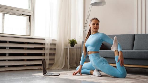 Schöne junge frau in einem blauen anzug, der fitnessübung zu hause tut. sie schaut auf ihren laptop und wiederholt die bewegungen für den online-kurs.
