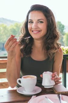 Schöne junge frau in einem café mit essen und trinken