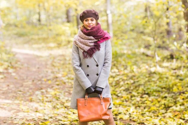 Schöne junge frau in einem grauen mantel und einer baskenmütze, die in der