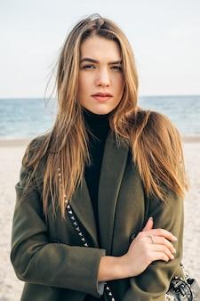 Schöne junge frau in einem grünen mantel am strand