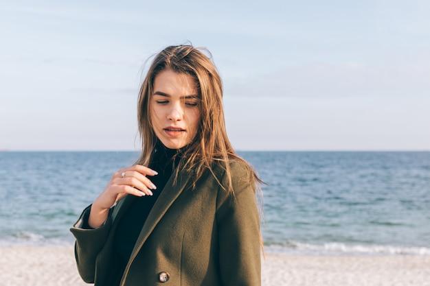 Schöne junge frau in einem grünen mantel, der entlang der küste geht