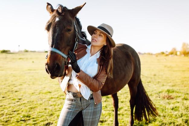 Schöne junge frau in einem hut und in den handschuhen mit einem broun pferd in einem feld auf einem sonnenuntergang