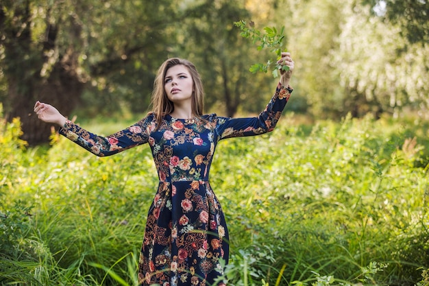 Schöne junge frau in einem kleid in den farben der natur mit einer pflanze in der hand