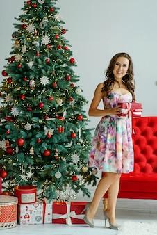 Schöne junge frau in einem kleid steht in der nähe eines weihnachtsbaumes mit einer geschenkbox in ihren händen und lächelt. weihnachts- und neujahrsfeiertagskonzept.