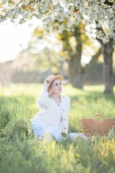 Schöne junge frau in einem korbhut ruht auf einem picknick in einem blühenden garten. weiße blumen. frühling. glück.