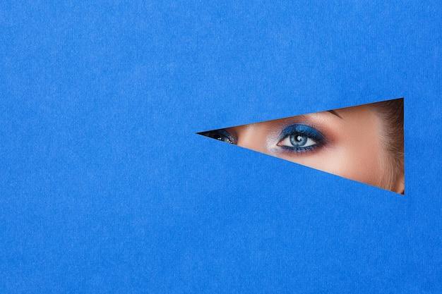 Schöne junge frau in einem loch im blauen papier, schönes helles make-up,