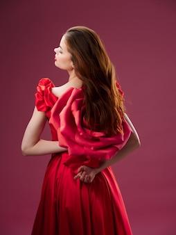 Schöne junge frau in einem luxuriösen kleid mit rosen, rosenblättern, stilvollem bild, rotem lippenstift