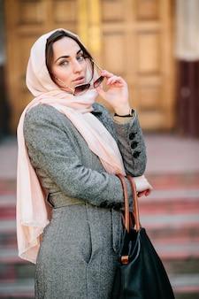 Schöne junge frau in einem mantel mit einer tasche, die aufwirft