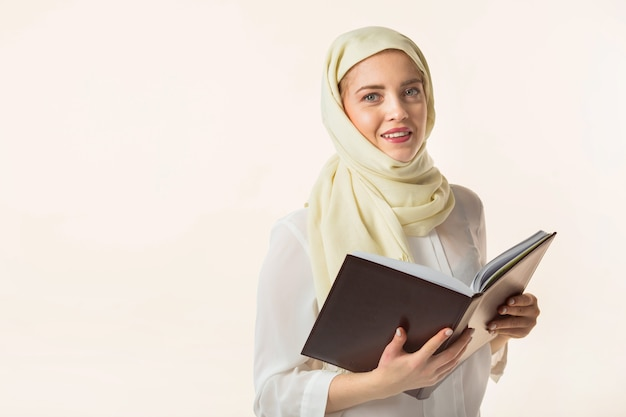 Schöne junge frau in einem muslimischen kopftuch auf einem weißen hintergrund