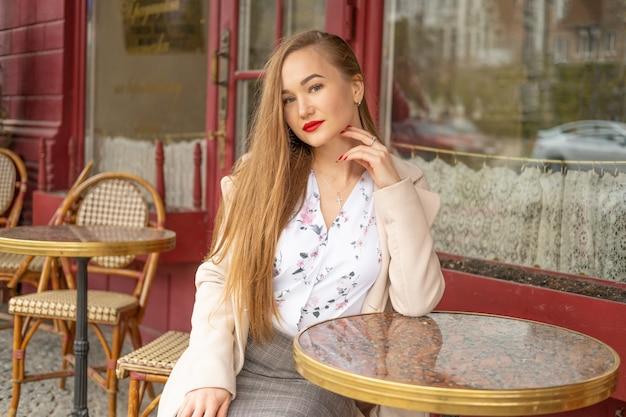 Schöne junge frau in einem pariser straßencafé