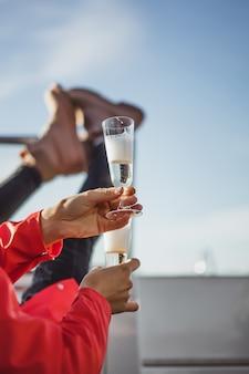 Schöne junge frau in einem roten mantel champagner auf einer yacht trinken.