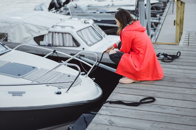 Schöne junge frau in einem roten mantel im yachthafen. stockholm, schweden