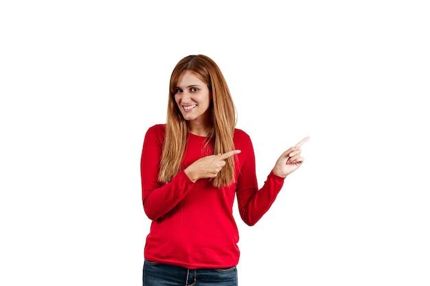 Schöne junge frau in einem roten pullover, ihre hände auf den copyspace zeigend, lokalisiert auf einem weißen hintergrund.