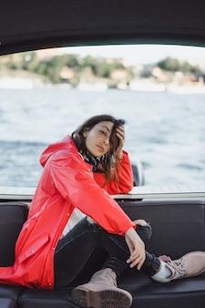 Schöne junge frau in einem roten regenmantel reitet eine private yacht. stockholm, schweden