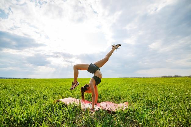 Schöne junge frau in einem schwarzen top und shorts führt einen handstand durch. ein model steht auf ihren händen und macht gymnastische spagat gegen den blauen himmel. gesundes lebensstilkonzept