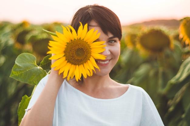 Schöne junge frau in einem sonnenblumenfeld. porträt einer jungen frau in der sonne. pollenallergie-konzept. im freien lebensstil glück
