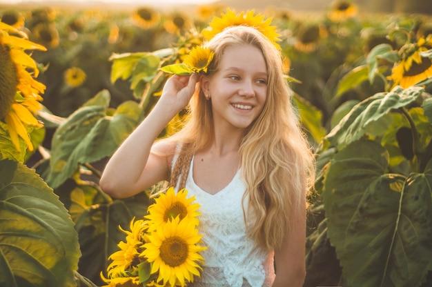 Schöne junge frau in einem sonnenblumenfeld. porträt einer jungen frau in der sonne. pollenallergie-konzept