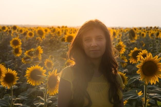 Schöne junge frau in einem sonnenblumenfeld