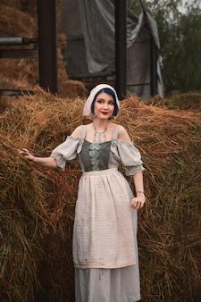 Schöne junge frau in einem traditionellen bayerischen kostüm steht in der nähe der heuhaufen auf dem bauernhof
