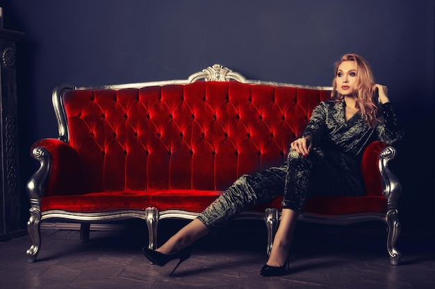 Schöne junge frau in einem veloursanzug sitzt auf einer roten vintage-couch.