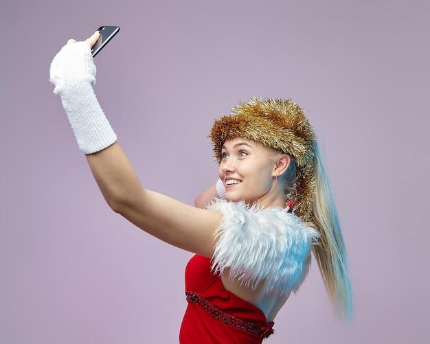 Schöne junge frau in einem weihnachtsmannkostüm hält ein smartphone und macht ein selfie