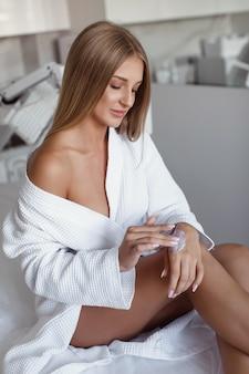 Schöne junge frau in einem weißen gewand trägt feuchtigkeitscreme auf ihre hände auf und sitzt auf einer couch in einem schönheitssalon. spa.