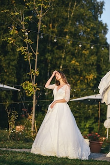 Schöne junge frau in einem weißen hochzeitskleid und in schwarzen stiefeln bei sonnenuntergang.