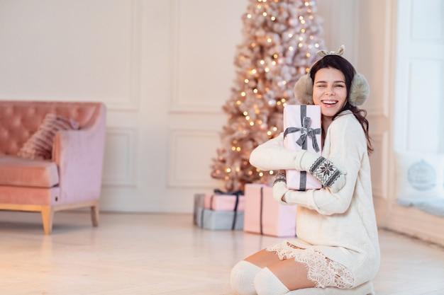 Schöne junge frau in einem weißen kleid wirft ein geschenk