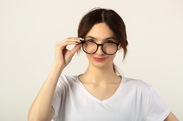 Schöne junge frau in einem weißen t-shirt auf einem weißen hintergrund, der brille trägt