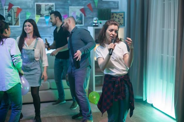 Schöne junge frau in einem weißen t-shirt, die karaoke auf einer party mit einer gruppe von freunden macht.
