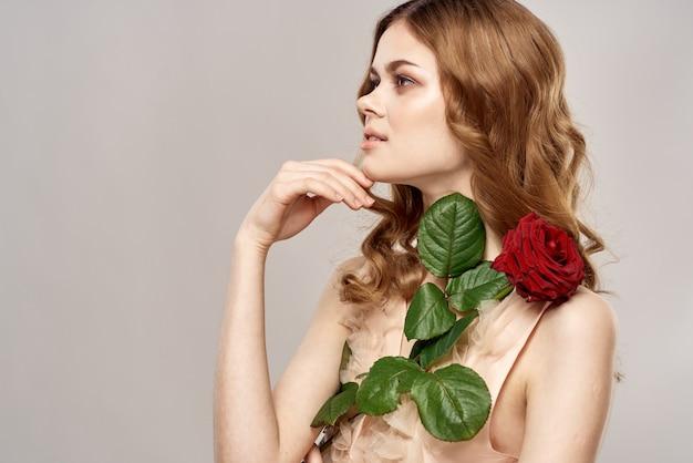 Schöne junge frau in einem zarten kleid mit einer scharlachroten rose in der hand, einem feiertag und einem geschenk