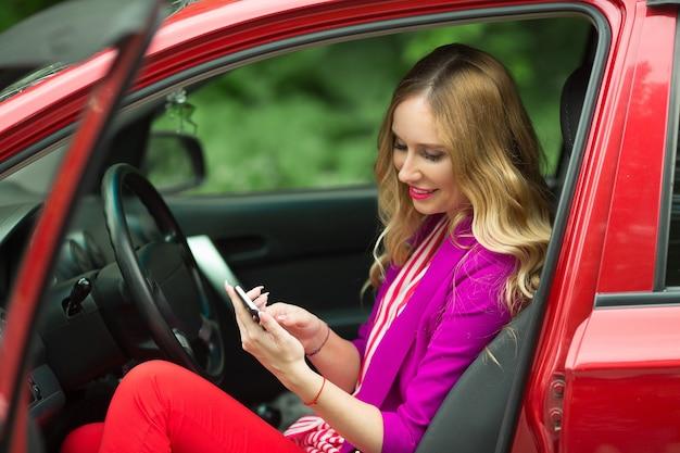 Schöne junge frau in einer jacke, die ein rotes auto mit einem telefon in seiner hand fährt
