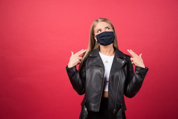 Schöne junge frau in einer medizinischen gesichtsmaske, die auf sich selbst zeigt