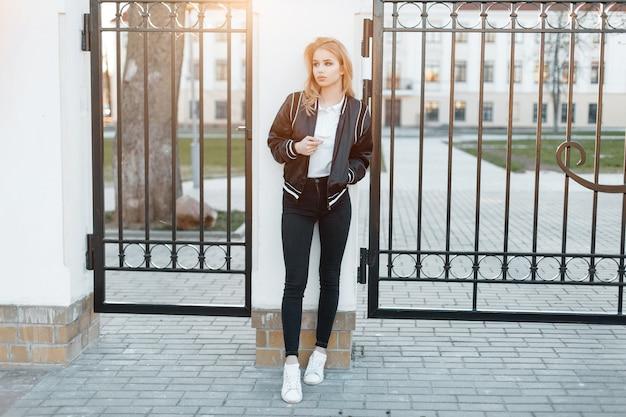 Schöne junge frau in einer stilvollen schwarzen jacke in einem weißen poloshirt in modischen jeans in weißen turnschuhen steht in der nähe der vintage-metalltore vor dem hintergrund des sonnenuntergangs. attraktives mädchen.