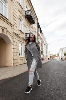 Schöne junge frau in einer stylischen oberbekleidung mit mantel, blau zerrissenen jeans, turnschuhen und einer tasche spaziert in der stadt