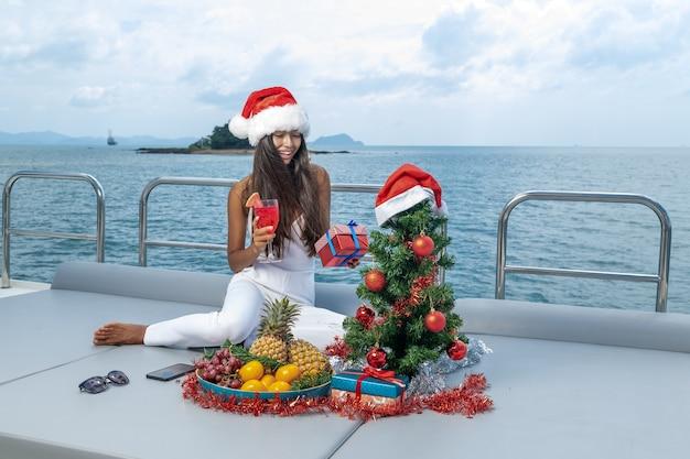 Schöne junge frau in einer weihnachtsmütze trinkt wassermelonensaft, während auf dem deck einer yacht sitzend.