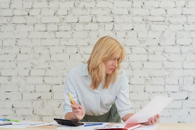 Schöne junge frau in eleganter freizeitkleidung arbeitet mit diagrammen und lächelt, während sie im büro steht. direktorin, die im büro arbeitet und geschäftsstatistiken analysiert, während sie diagramme hält.